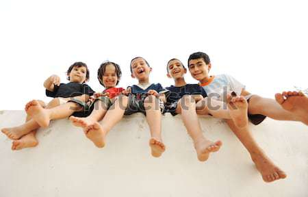 Five happy friends sitting on wall outdoor Stock photo © zurijeta