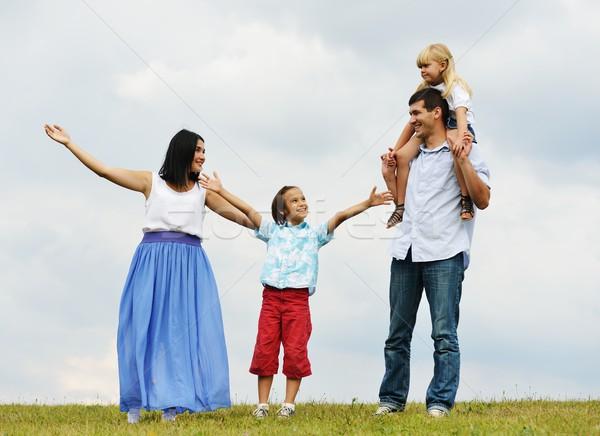 Happy family in nature walking on green summer meadow Stock photo © zurijeta