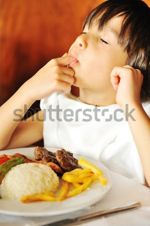 Real enjoying food, cute kid with finger in his mouth Stock photo © zurijeta