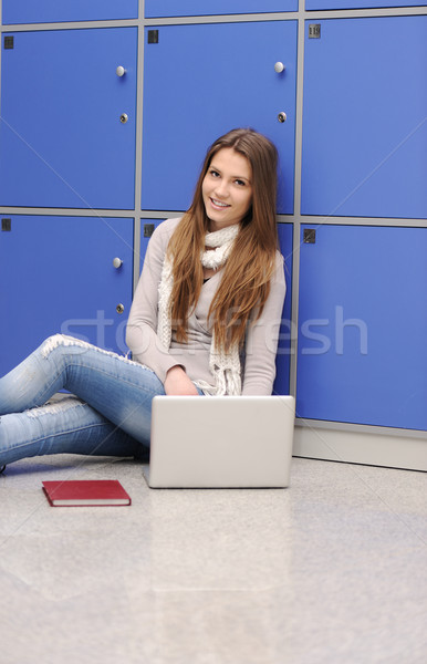 Beautiful female student sitting on ground with laptop and leaning on lockers Stock photo © zurijeta