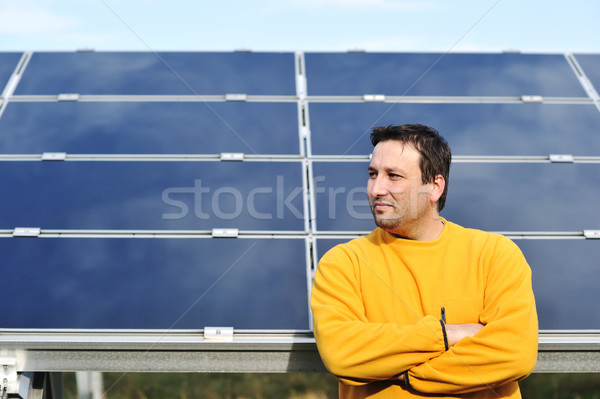 Young male worker with solar panels in background Stock photo © zurijeta