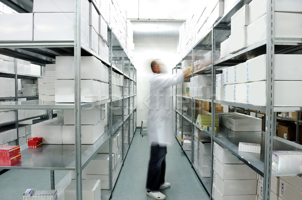 Worker putting boxes together on shelves in modern warehouse Stock photo © zurijeta