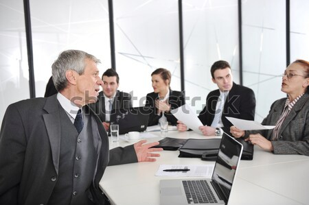 Senior businessman at a meeting. Group of colleagues in the background Stock photo © zurijeta