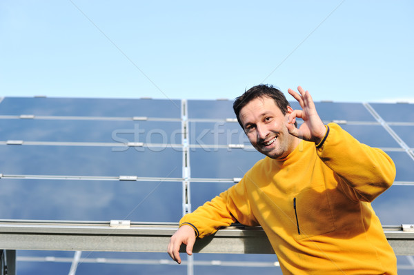 Young male engineer with solar panels in background Stock photo © zurijeta