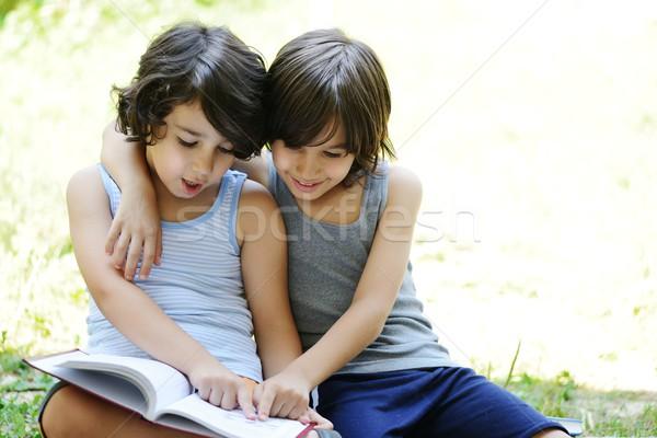 Peu garçon lecture livre extérieur deux Photo stock © zurijeta
