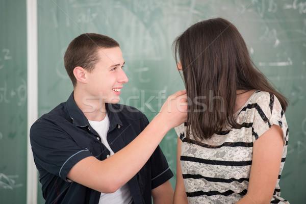 Iskolás lány beszél férfi osztálytárs mosolyog iskolatábla Stock fotó © zurijeta