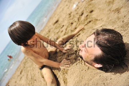 Stock photo: Real happiness, playing on beach: my dad under the sand