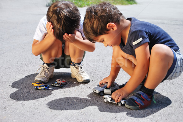 Toys cars in front of children legs and one of them is crying Stock photo © zurijeta