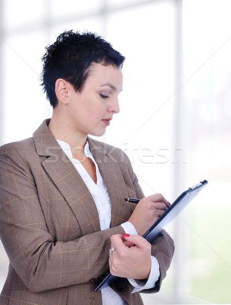 Portrait of a young female entrepreneur taking notes inside a modern building with big glass windows Stock photo © zurijeta