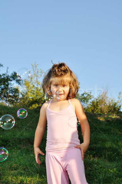 Meisje zeepbellen naar camera gras tuin Stockfoto © zurijeta