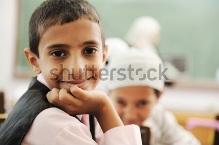 Positive kid in classroom smiling and looking in camera Stock photo © zurijeta