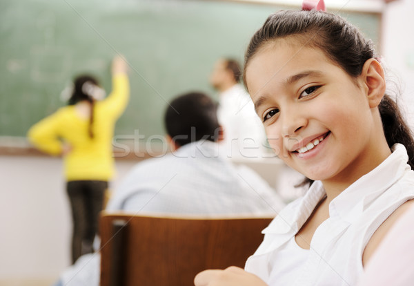 Adorable girl smiling in school classroom and behind her class activities Stock photo © zurijeta