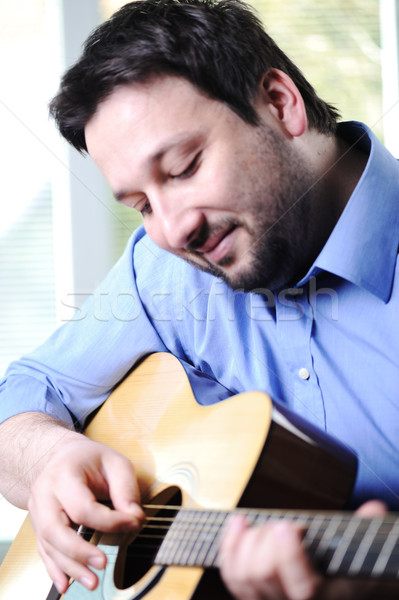 Man playing guitar and relaxing at home Stock photo © zurijeta