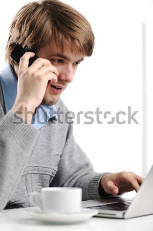 Young man speaking on cell phone and working on laptop Stock photo © zurijeta