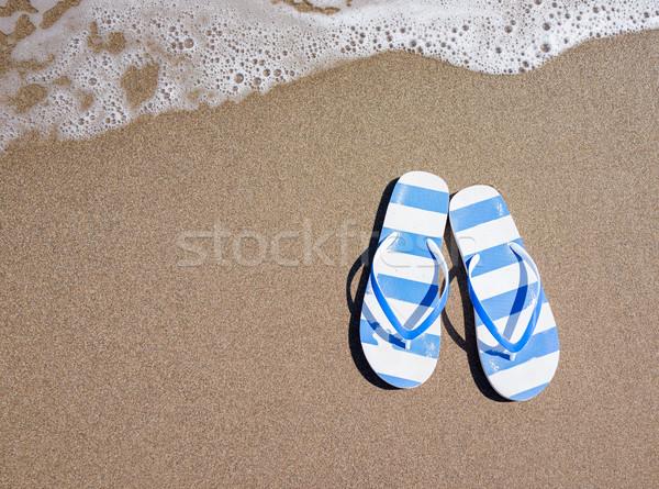 Flip flops on a sandy ocean beach Stock photo © zurijeta