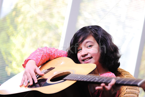 Little girl playing guitar at home Stock photo © zurijeta