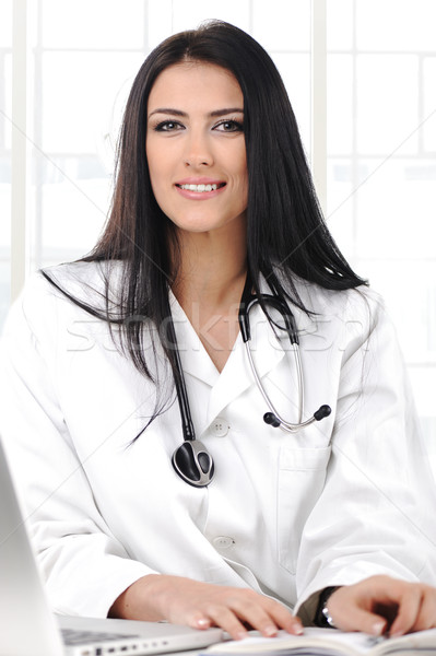 Young doctor woman looking to camera with smile, sitting on her desk Stock photo © zurijeta
