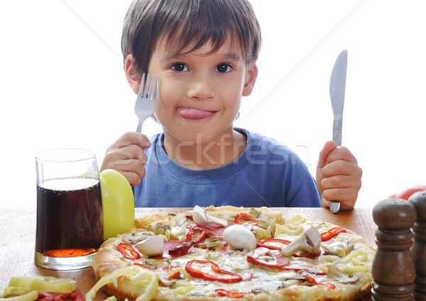 Bonitinho pequeno menino alimentação pizza tabela Foto stock © zurijeta