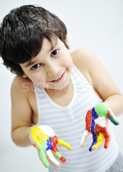 Stock photo: Little boy with hands painted in colorful paints ready for hand