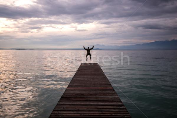 Saltando homem passarela manhã nuvens Foto stock © zurijeta