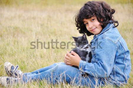 Very cute little girl with cat on meadow Stock photo © zurijeta