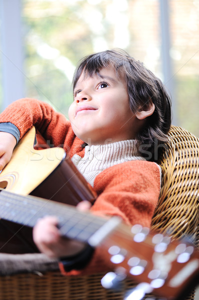 Stock photo: Portrait of young boy playing acoustic guitar at home