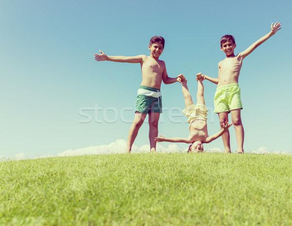 Irmãos jogar de cabeça para baixo verde prado família Foto stock © zurijeta