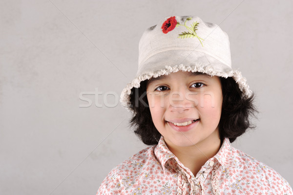 Smiling girl showing teeth wearing a  hat with red flower Stock photo © zurijeta