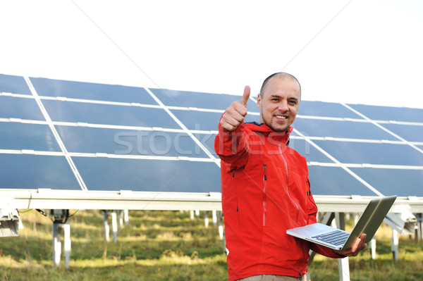 Male engineer using laptop, solar panels in background Stock photo © zurijeta