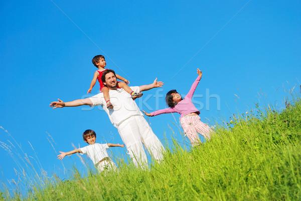 Happy family with four members on beautiful scene in nature Stock photo © zurijeta