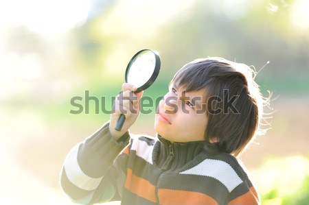Happy kid exploring nature with magnifying glass Stock photo © zurijeta
