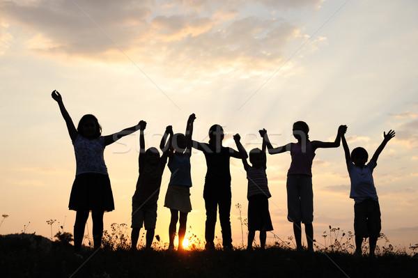 Group of happy children playing at summer sunset Stock photo © zurijeta