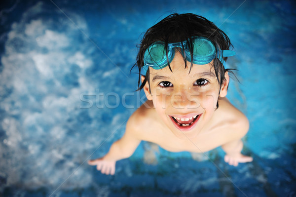 Stock photo: Little boy at swimming pool with goggles