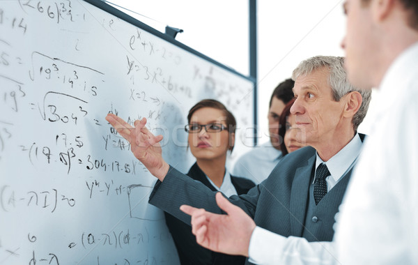 Senior project leader explaining formula to younger colleagues Stock photo © zurijeta