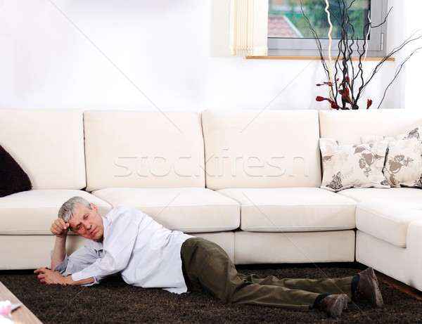 Elderly man having heart attack lying on floor at home Stock photo © zurijeta