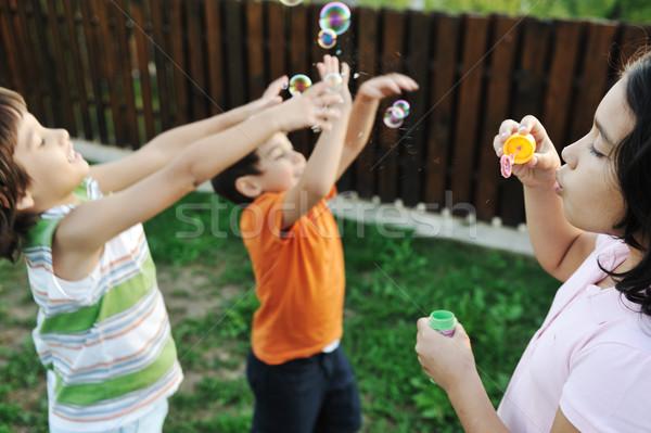 Foto stock: Feliz · crianças · jogar · bubbles · ao · ar · livre · foco