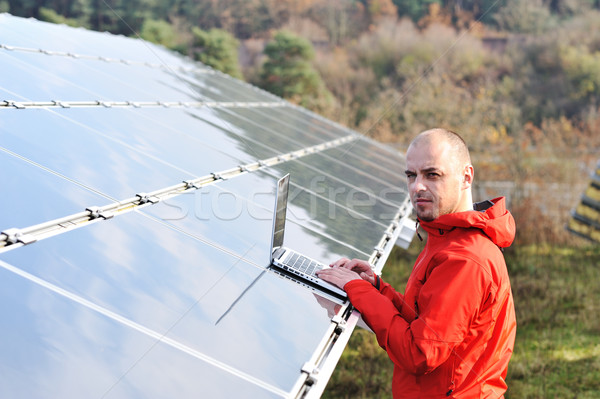 Stock photo: Male engineer using laptop, solar panels in background
