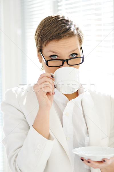 Young business woman drinking coffee at office Stock photo © zurijeta