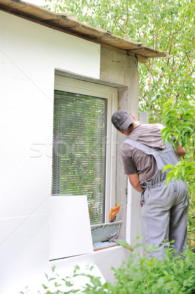 Construction worker applying insulation over exterior wall of house Stock photo © zurijeta