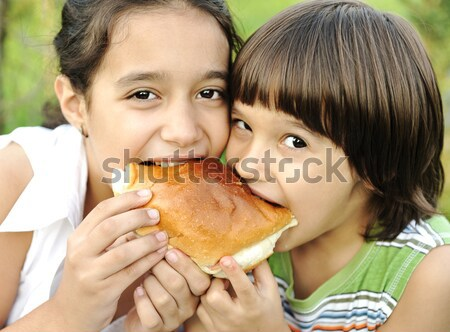 Closeup of two children eating sandwich in nature together, healthy food, careless and love Stock photo © zurijeta