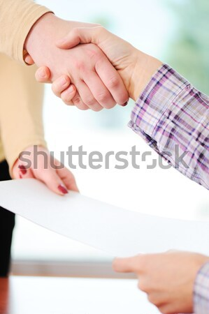 Closing a deal with a handshake. Signed contract in the hand between women. Stock photo © zurijeta