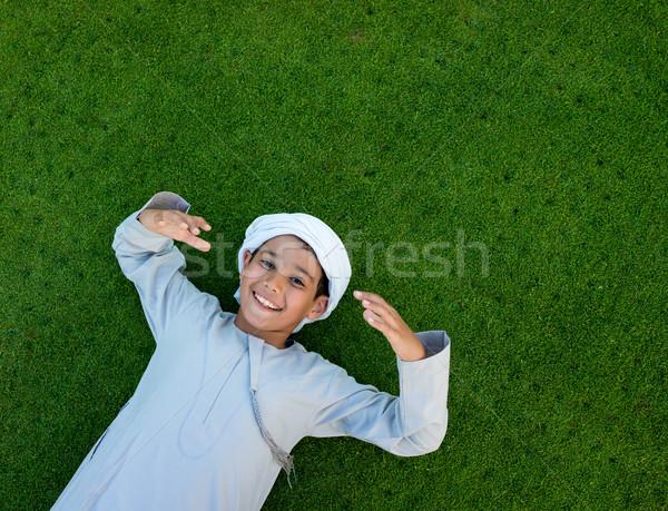 Happy Arabic kid on green grass Stock photo © zurijeta