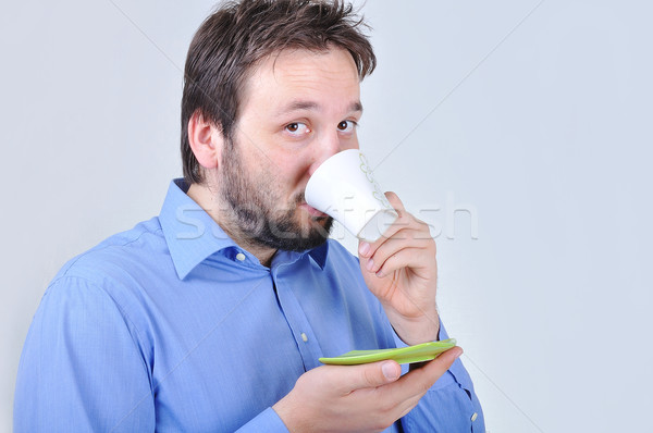 Young attractive man is drinking a cup of coffey Stock photo © zurijeta