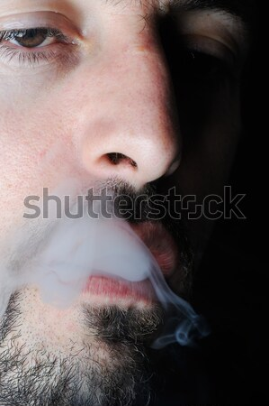 Man in dark exhaling cigarette smoke Stock photo © zurijeta