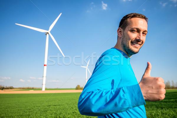Férfi szélturbina mező áll hüvelykujj felfelé Stock fotó © zurijeta