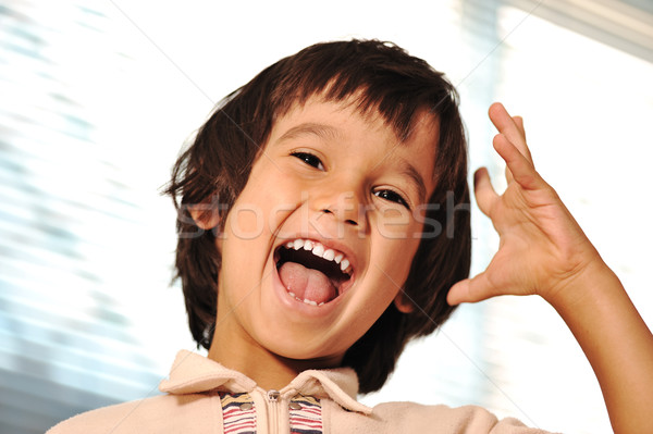 Happy child indoor with hand gesture Stock photo © zurijeta