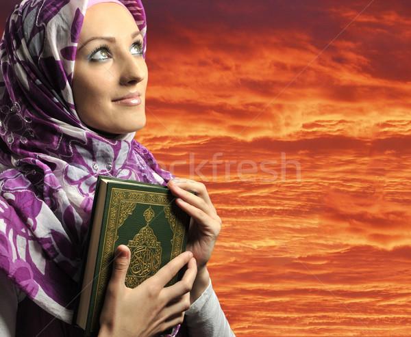 Adorable Muslim girl holding holy book Koran, against red sky Stock photo © zurijeta