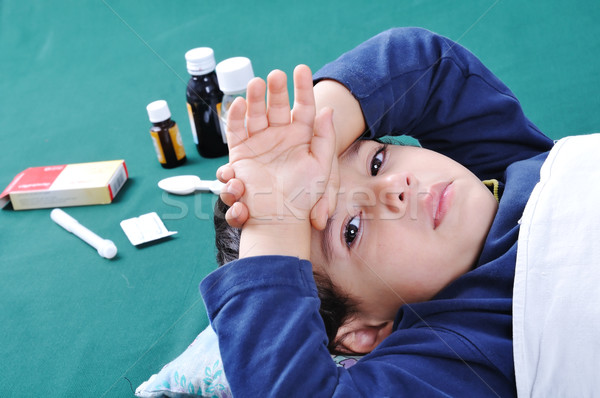 Sick child with medics and pills behind him Stock photo © zurijeta