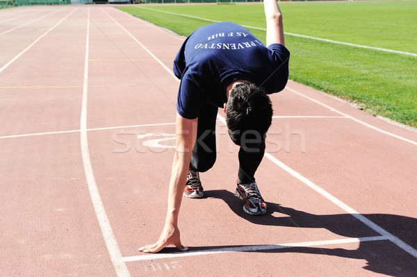 young male  athlete is at the start of the treadmill at the stadium Stock photo © zurijeta