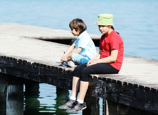 Boy and girl by the wooden dock on a beautiful sea Stock photo © zurijeta